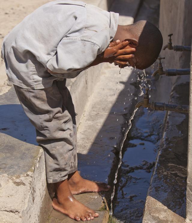 Boy washing his face